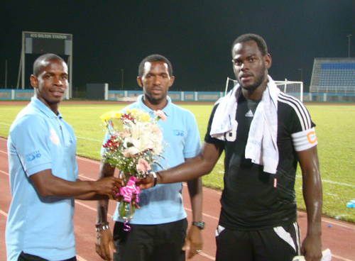 Photo: W Connection captain Jan-Michael Williams (right) receives a token of solidarity from North East Stars players Anthony Wolfe (left) and Charles Pollard.