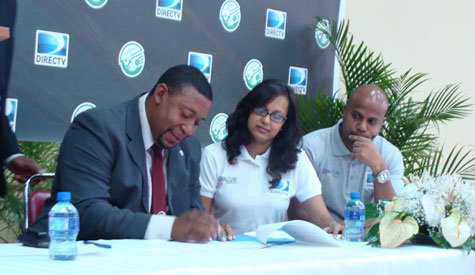 Photo: W Connection owner David John Williams (left) signs a sponsorship deal with DIRECTV marketing manager Tamara Ragoonath (centre).