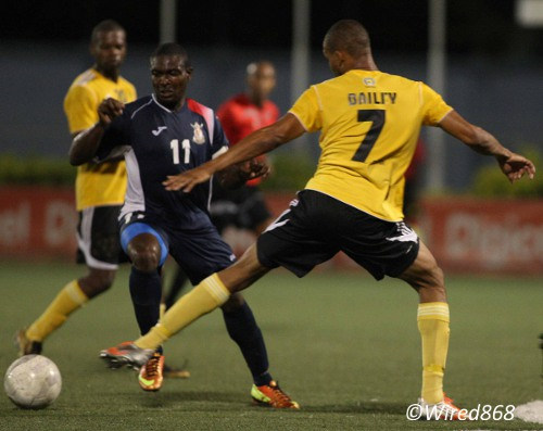 Photo: Defence Force attacker Kevon Carter (left) glides past T&TEC FC defender Cebastian Bailey. (Courtesy Wired868)