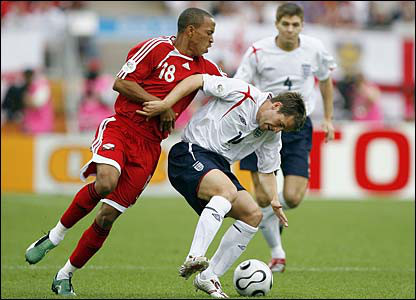 Photo: Trinidad and Tobago midfielder Densill Theobald (left) harasses England star Michael Owen during the 2006 World Cup.
