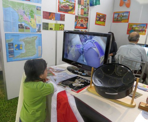 Photo: A Peruvian boy sees something he likes in a T&T Carnival DVD. (Courtesy Juliet Solomon/Wired868)