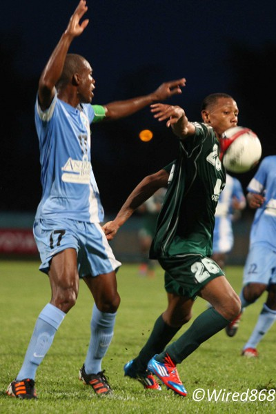 Photo: W Connection and Suriname winger Stefano Rijssel (right) controls the ball while Antigua Barracuda captain George Dublin calls for help during the 2013 Caribbean Cup. (Courtesy Wired868)