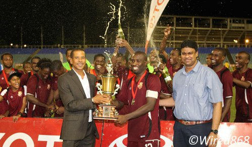 Photo: North East Stars striker Cornell Glen (centre) lifts the Toyota Classic Cup from Pro League CEO Dexter Skeene (left). Toyota marketing manager Sean Shaffie looks on. (Courtesy Wired868)
