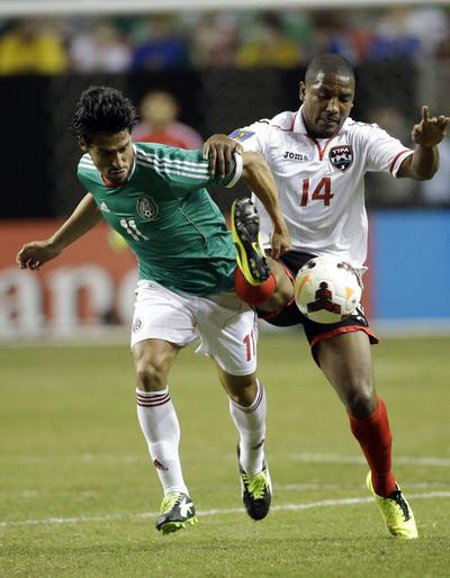 Photo: Trinidad and Tobago midfielder Andre Boucaud (right) hustles Mexico attacker Rafael Marquez Lugo off the ball during the 2013 CONCACAF Gold Cup. (Courtesy CONCACAF)