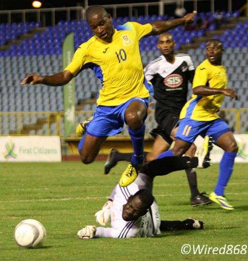 Photo: Central FC goalkeeper Jan-Michael Williams (on the ground) denies Defence Force midfielder Josimar Belgrave during the First Citizens Cup final. (Courtesy Wired868)