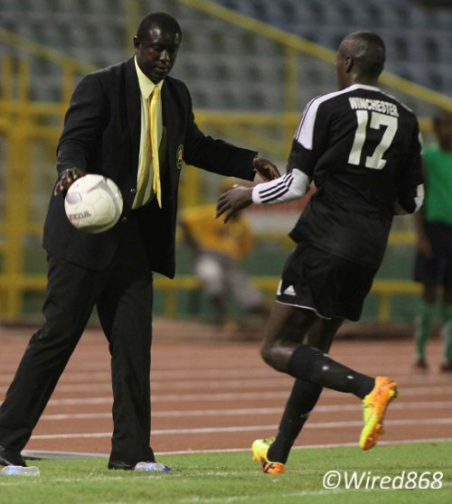 Photo: Central FC striker Rundell Winchester (right) gave Defence Force coach Ross Russell another glimpse of his ability in the First Citizens Cup final. (Courtesy Wired868)