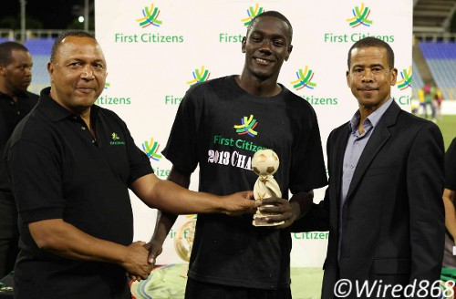 Photo: Central FC striker Rundell Winchester (centre) receives the MVP award from a First Citizens representative while Pro League CEO Dexter Skeene (right) looks. (Courtesy Wired868)