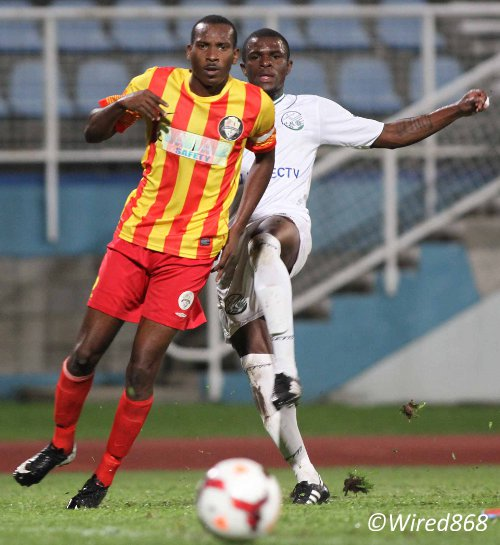 Photo: Point Fortin right back Garyl Doldron (left) is pressured for possession by W Connection attacker Jerrel Britto. (Courtesy Wired868)