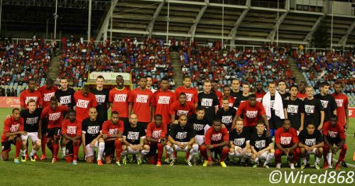 "Photo: The Trinidad and Tobago and New Zealand football teams pose in Native Spirit ""I support Akeem Adams"" tee-shirts before kick off at the Hasely Crawford Stadium in October 2013. (Courtesy Wired868)"