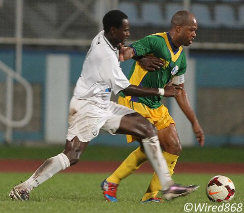 Photo: Guaya United captain Ryan Stewart (right) holds off W Connection midfielder Silvio Spann during the 2013 Toyota Cup. (Courtesy Wired868)