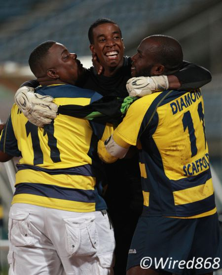 Photo: Club Sando custodian Andre Marchan (centre) celebrates with team captain Teba McKnight (right) and a supporter after helping his team to Toyota Classic penalty kicks win over Caledonia AIA. (Courtesy Allan V Crane/Wired868)