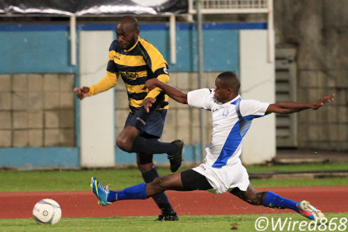 Photo: Club Sando captain Teba McKnight (left) evades a lunge from a Police defender. Police had three players ejected last night as they lost 3-1 to Sando. (Courtesy Allan V Crane/Wired868)