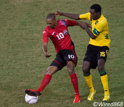 Photo: Trinidad and Tobago midfielder Ataullah Guerra (left) spins away from Jamaican captain Je-Vaughn Watson. (Courtesy Allan V Crane/Wired868)