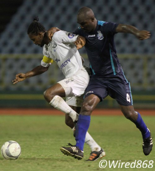 Photo: W Connection captain Gerard Williams (left) tries to sneak past Police FC defender Karlon Murray. (Courtesy Wired868)