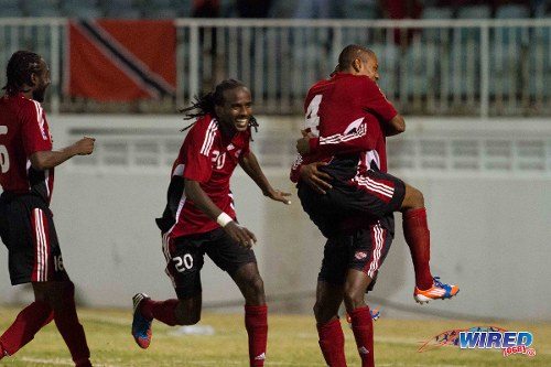 "Photo: Trinidad and Tobago defender Seon Power (second from left) and midfielder Keyon Edwards (far left) join the celebrations as the ""Soca Warriors"" book their place in the 2012 Caribbean Cup final in Antigua. (Courtesy Allan V Crane/Wired868)"