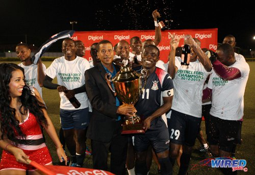 Photo: Stand-in Defence Force captain Kevon Carter (centre) takes the 2012/13 Pro League title from Pro League CEO Dexter Skeene. (Courtesy Wired868)