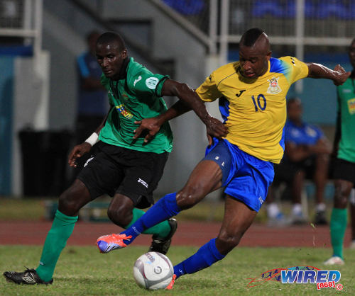 Photo: San Juan Jabloteh player Nyron Jones (left) tries to keep a grip on Defence Force player Josimar Belgrave. (Courtesy Allan V Crane/ Wired868)