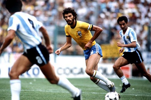 Photo: Brazil midfielder general Socrates (centre) runs into space between Argentina midfielder Osvaldo Ardilles (right) and his teammate. (Courtesy Times.co.uk)