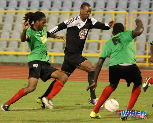 Photo: Central playmaker Ataullah Guerra (centre) runs at the San Juan Jabloteh defence. Guerra was subbed after half hour yesterday due to a shoulder injury.  (Courtesy Wired868)