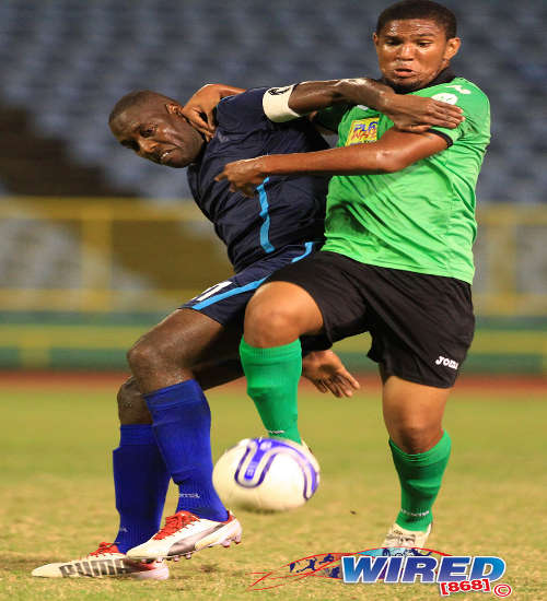 Photo: Police FC captain Todd Ryan (left) wrestles for possession with San Juan Jabloteh midfielder Jean-Luc Rochford. (Courtesy Allan V. Crane/ Wired868)