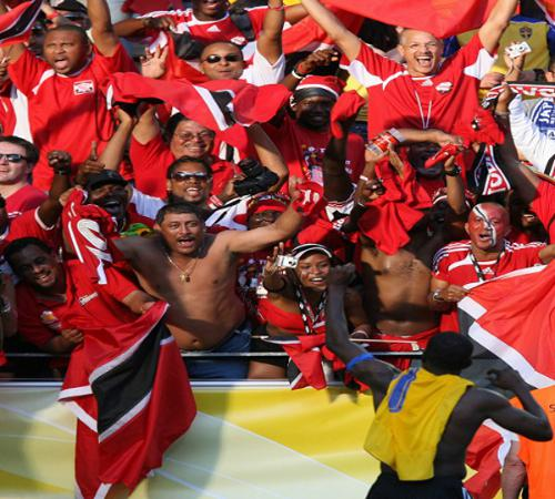 "Photo: Trinidad and Tobago football captain and legend Dwight Yorke (bottom) salutes the ""Soca Warriors"" fans at the 2006 Germany World Cup. (Copyright AFP 2014/Patrik Stollarz)"
