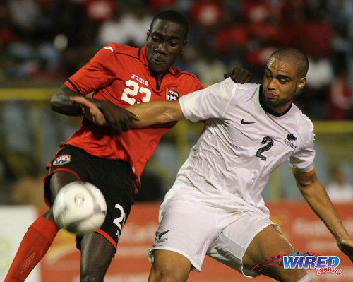 Photo: Trinidad and Tobago attacker Rundell Winchester (left) tussles with New Zealand captain and ex-West Ham defender Winston Reid during a senior international friendly at the Hasely Crawford Stadium in December 2013. Winchester's transfer to CS Vise is likely to be investigated by the TTFA. (Courtesy Wired868)