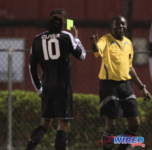 Photo: Veteran Central FC midfielder Marvin Oliver (left) gives referee Gyasi McDonald his yellow card back. McDonald was one of several top flight officials who were missing in action yesterday. (Courtesy Allan V Crane/ Wired868)