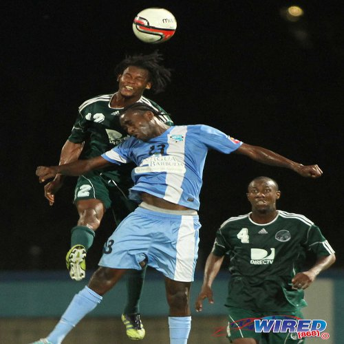 Photo: DIRECTV W Connection captain and St Kitts and Nevis international Gerard Williams (left) wins a header against an Antigua Barracuda opponent while Daneil Cyrus (right) looks on during the 2012 Caribbean Club Championship. (Courtesy Wired868)