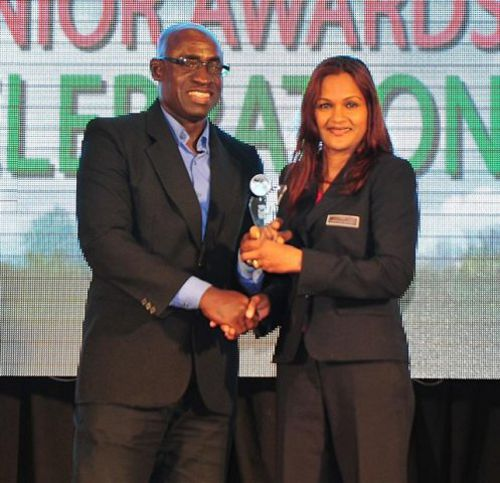 Photo: Cindy Mohammed (right) receives the 2012/13 Pro League Referees' Assistant of the Year award from former Trinidad and Tobago national football captain Clayton Morris. (Courtesy TT Pro League)