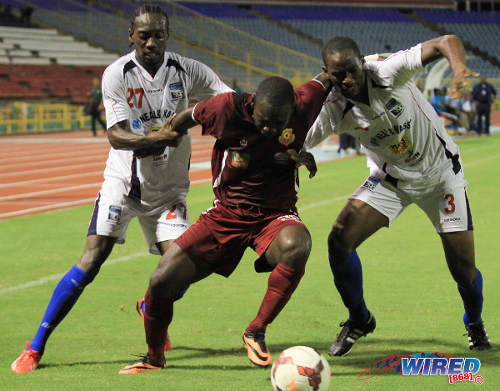 Photo: North East Stars striker Trevin Caesar (centre) holds off Caledonia AIA players Nathan Lewis (left) and Nuru Muhammad during a Pro League fixture. (Courtesy Allan V Crane/ Wired868)