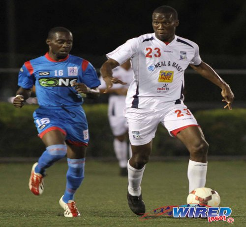 Photo: Caledonia AIA forward Jamal Gay (right) weighs up his options while St Ann's Rangers attacker Kennedy Isles looks on. (Courtesy Wired868)