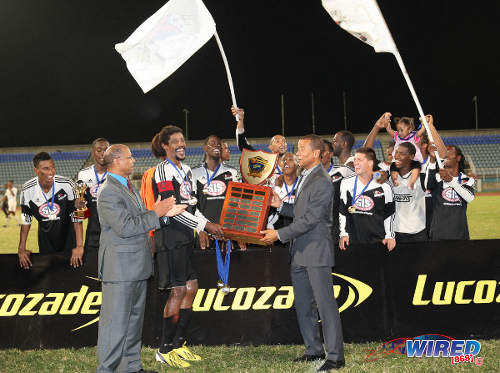 Photo: Central FC captain Marvin Oliver (centre) takes the Lucozade Sport Goal Shield trophy from Pro League CEO Dexter Skeene while a Lucozade official looks on. (Courtesy Allan V Crane/Wired868)