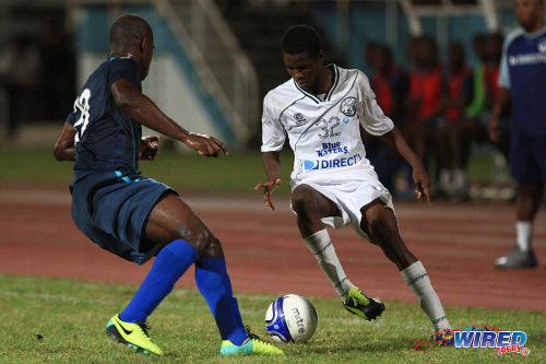 Photo: W Connection attacker Dimitrie Apai (right) takes on Police FC utility player Elijah Belgrave during a 2013/14 Pro League fixture. (Courtesy Allan V Crane/Wired868)