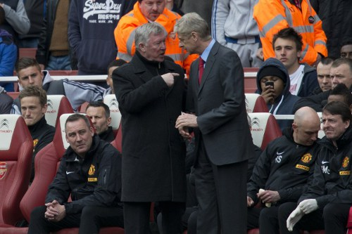 Photo: Former Manchester United manager Sir Alex Ferguson (left) exchanges words with his Arsenal counterpart Arsene Wenger. (Copyright AFP 2014/Adrian Dennis)