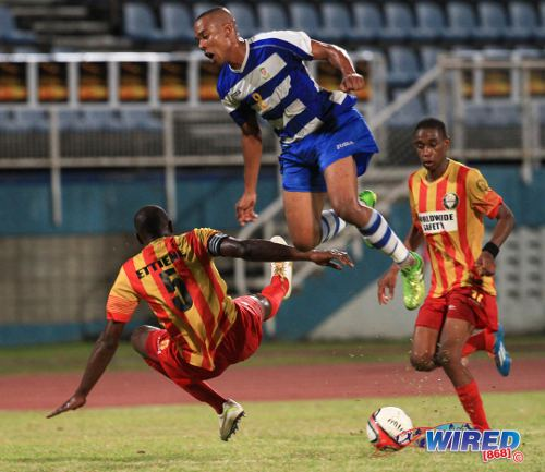 Photo: Point Fortin Civic defender and captain Andre Ettienne (left) forces Defence Force midfielder Curtis Gonzales (centre) to take evasive action. (Courtesy Allan V Crane/Wired868)
