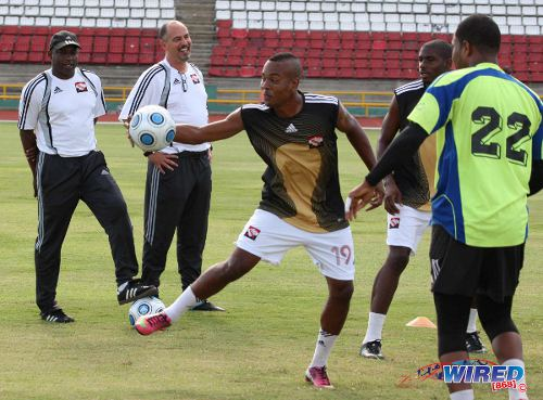 Photo: Trinidad and Tobago head coach Stephen Hart (second from left) shares a light moment with assistant coach Hutson Charles (far left) and national players (from right to left) Cleon John, Kareem Moses and Curtis Gonzales during a training session in 2013. (Courtesy Wired868)