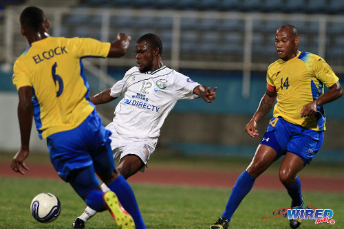 Photo: Defence Force defender Rodell Elcock (left) dives in to block a shot from W Connection attacker Jerrel Britto (centre) while Defence Force captain Cory Rivers looks on. (Courtesy Allan V Crane/Wired868)
