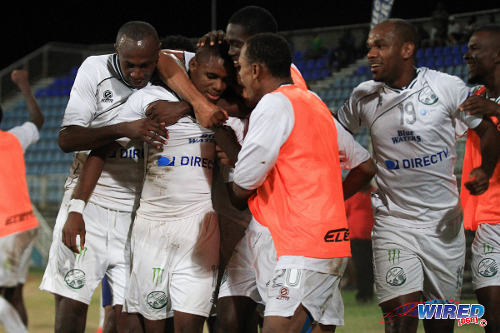 Photo: W Connection playmaker Joevin Jones (centre) is congratulated by teammates during their decisive Pro League win against Defence Force. (Courtesy Allan V Crane/Wired868)