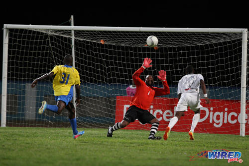 Photo: W Connection star Joevin Jones (right) dinks the ball over Defence Force goalkeeper Kevin Graham (centre) while his teammate Thurlani George looks on helplessly at the Ato Boldon Stadium. (Courtesy Allan V Crane/Wired868)