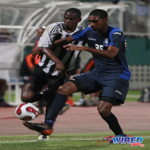 Photo: Weslie John (right) tries to hold off Central FC attacker Anthony Wolfe during his stint with Police FC. (Courtesy Wired868)