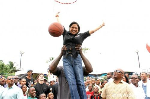 Photo: Trinidad and Tobago Prime Minister Kamla Persad-Bissessar is lifted airborne to take a shot by former NBA star Shaquille O'Neal. (Courtesy Newsday)