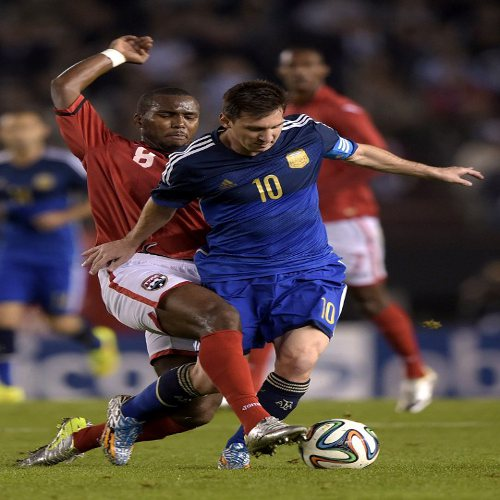 Photo: Argentina captain Lionel Messi (right) is tackled by Trinidad and Tobago midfielder Khaleem Hyland during their international fixture in Buenos Aires on 4 June 2014. (Copyright AFP 2014/ Juan Mabromata)