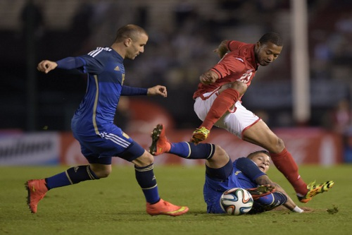 Photo: Trinidad and Tobago winger Lester Peltier (right) vies for the ball with Argentina defender Marcos Rojo (bottom) and forward Rodrigo Palacio. (Copyright AFP 2014/ Juan Mabromata)
