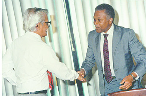 Photo: Late Prime Minister Arthur NR Robinson (right) is greeted by then Cabinet colleague Basdeo Panday. (Courtesy Trinidad Guardian)
