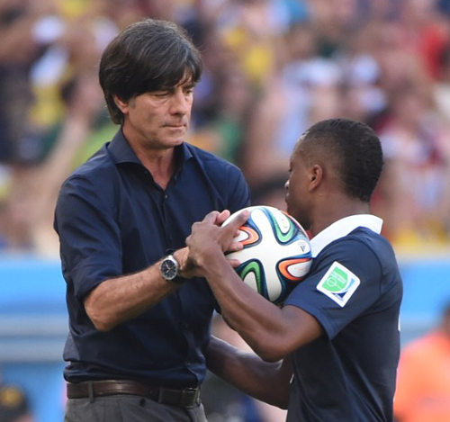 Photo: Can we play football monsieur? Germany coach Joachim Löw (left) tries to keep the ball from France defender Patrice Evra. (Copyright AFP 2014/Patrik Stollarz)