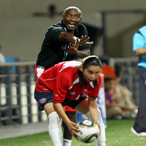 Photo: Trinidad and Tobago women's coach Marlon Charles (background) instructs his team during an international fixture against Chile in the Singapore 2010 Youth Olympic Games (YOG) at the Jalan Besar Stadium in Singapore, Aug 12, 2010.  Chile won 1-0.  (Courtesy SPH-SYOGOC/Seyu Tzyy Wei)