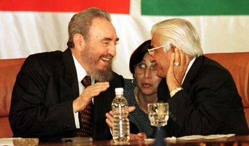 Photo: Former Trinidad and Tobago prime minister Basdeo Panday (right) shares a joke with then Cuba president Fidel Castro during the closing ceremony of a CARIFORUM meeting in 1998.   (Copyright AFP 2014/Roberto SCchmidt)