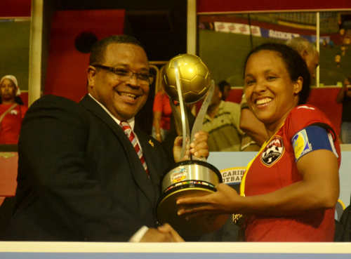 Photo: Trinidad and Tobago captain Maylee Attin-Johnson (right) collects the 2014 Caribbean Cup trophy from CFU president Gordon Derrick. (Courtesy Jinelle James/WOLF)