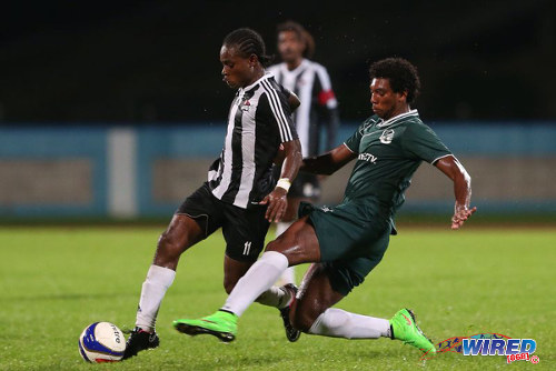 Photo: Central FC midfielder Darren Mitchell (left) tries to evade a tackle from W Connection forward Jamal Clarence in the 2014 Charity Shield. (Courtesy Allan V Crane/Wired868)