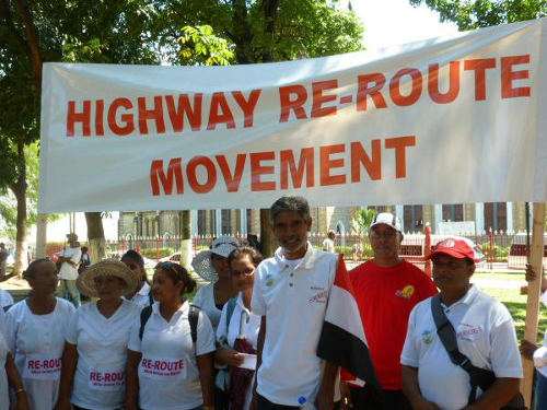 Photo: Dr Wayne Kublalsingh (centre) and the Highway Re-Route Movement.